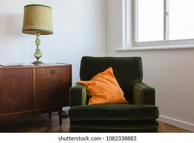 Retro living room furniture of a green velvet armchair and mid c