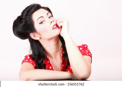 Retro look pin-up brunette girl flirting her finger touch her mouth studio shot pink background