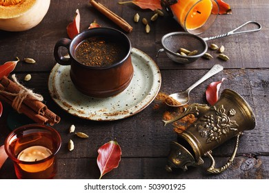 Retro looking image of cup of spiced coffee and fall themed items over dark rustic background. Lifted shadows, color toning