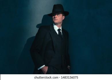 Retro man in hat wears suit and tie.