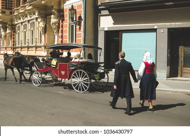 retro man and woman walking on street behind carriage