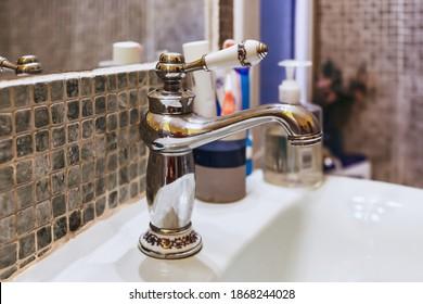 Fauceta de metal retro en el lavabo, interior del baño