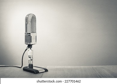 Retro microphone from 50s on table. Vintage old style sepia greyscale photo