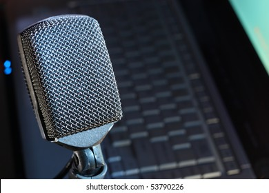 Retro microphone in focus, with laptop soft background.  Plenty of copy space to list your website, podcast or audio stream.