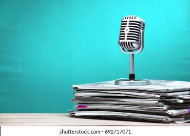 Retro microphone with newspaper on wooden table announcement concept