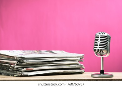 Retro microphone with newspaper on wooden table - announcement concept