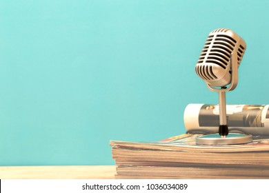 Retro microphone with old magazine on wooden table vintage stlye