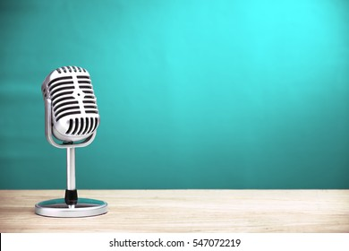 Retro microphone on wooden table with turquoise wall background