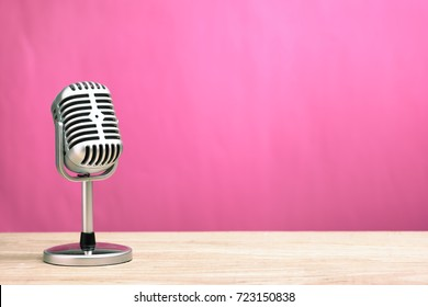 Retro microphone on wooden table with pink wall background