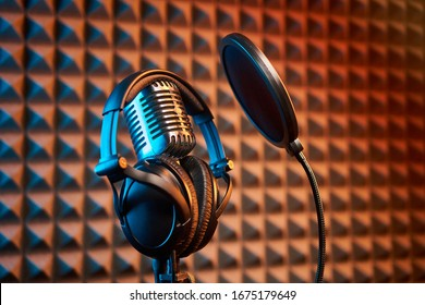 Retro microphone with professional headphones with pop filter for singing or recording a podcast on acoustic foam panel background, colorful light