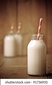 Retro milk bottle with striped drinking straw and further bottles in background