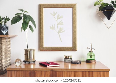Retro and minimalistic interior with mock up photo frame on the vintage brown shelf, hanging plant in design pot, notebook, sprinkler for platns, gold organizer, avocado plant and accessories.