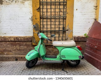 Retro motor scooter in mint green color and old brick wall with peeling paint as background in Seville, Spain