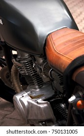 Retro motorcycle and details. Glossy metal and matte textures. Soft colors. Saddle and storage.