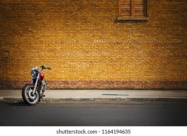 retro motorcycle parked in front of brick wall