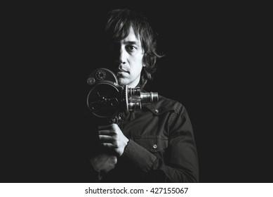 Retro movie camera. Guy takes on a retro movie camera. Black and white photography.