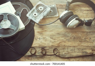 Retro music background, vinyl records, film reel, audio cassettes, headphones on an old wooden table, sepia toned