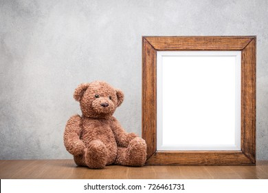 Retro oak wooden photo frame blank and Teddy Bear toy on table front concrete wall background. Vintage old style filtered photography