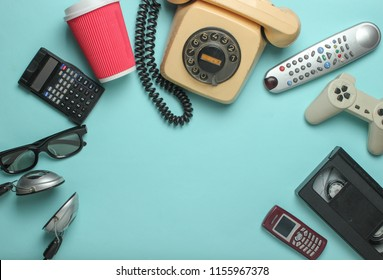 Retro objects on blue background. Rotary telephone, audio cassette, video cassette, gamepad,calculator, tv remote, headphones, push-button phone. Analog media technology of  past. Copy space.