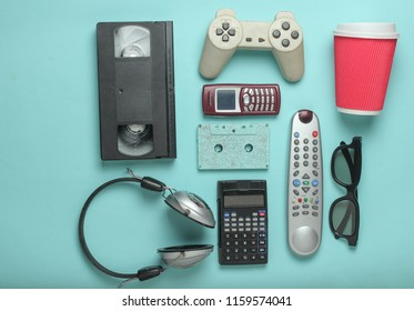 Retro objects on blue background. 3d glasses, audio cassette, video cassette, gamepad,calculator, tv remote, headphones, push-button phone. Analog media technology of  past. Flat lay.