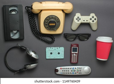 Retro objects on gray background. Rotary telephone, audio cassette, video cassette, gamepad, 3d glasses, tv remote, headphones, push-button phone. Analog media technology of the past. Flat lay.
