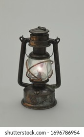 retro oil lamp, illuminated, isolated, closeup on gray background, vertical