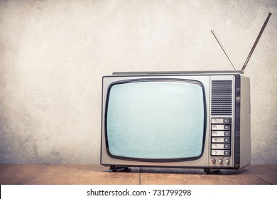 Retro old analog TV set receiver with monochrome static noise on display front textured concrete wall background. Television broadcasting concept. Vintage aged style filtered photo