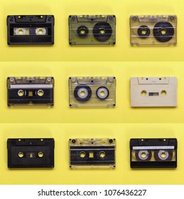 Retro old compact audio cassette tapes on yellow background - vintage technology background