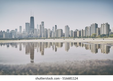 Retro old film stylized Chicago city skyline reflected in a puddle, USA.