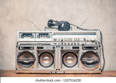 Retro old ghetto blaster stereo radio cassette tape recorder boombox from circa 1980s and headphones front concrete wall background. Vintage instagram style filtered photo