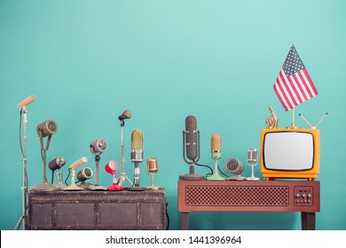 Retro old microphones from 50s and 60s for press conference or interview, outdated TV from 70s, USA flag, golden index finger front gradient aquamarine  wall background. Vintage style filtered photo