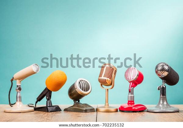Retro alte Mikrofone für Pressekonferenz oder Interview auf Tischfront Farbverlauf Aquamarine Hintergrund. Vintage altes gefiltertes Foto