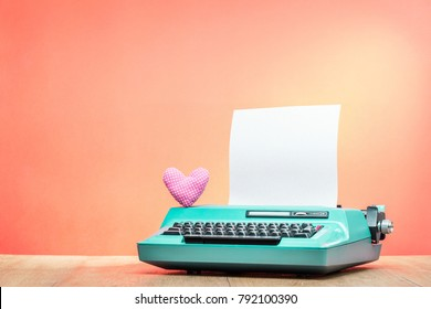 Retro old mint green typewriter with paper sheet and handmade heart shape on wooden desk front gradient background. Valentines day love letter concept. Vintage instagram style filtered photo
