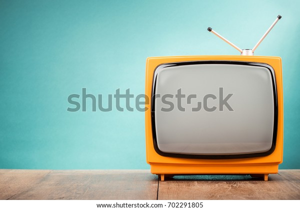 Retro old orange TV receiver on table front gradient aquamarine wall background. Vintage style filtered photo