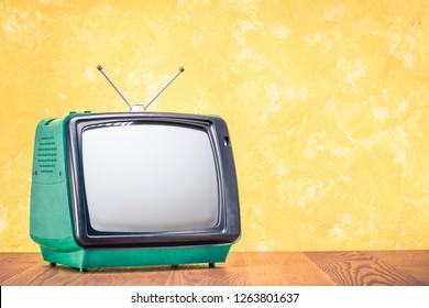 Retro alte veraltete grüne TV-Empfänger aus ca. 70 Jahren auf Holztisch vorn strukturiert gelben Betonwandhintergrund. Vintage-gefiltertes Foto