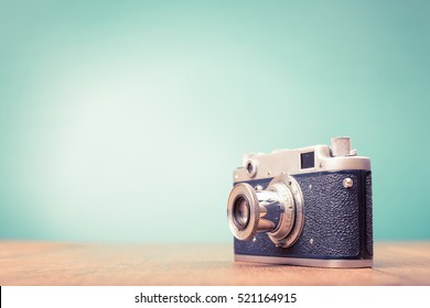 Retro old outdated rangefinder film camera from 50s on table front mint green background. Vintage style filtered photo
