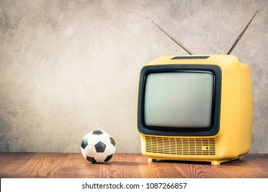 Retro old outdated yellow tube TV receiver and soccer ball on wooden table front textured aged grunge concrete wall background. Vintage style filtered photo