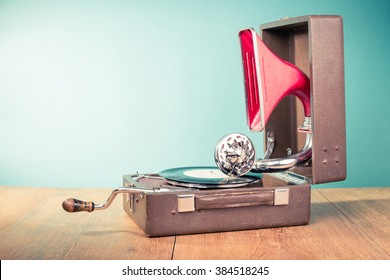 Retro old portable phonograph front mint green background. Vintage style filtered photo
