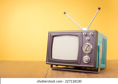 Retro old portable television from 80s front gradient yellow background