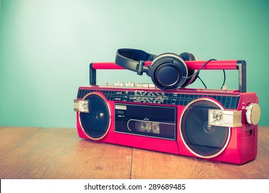 Retro old radio cassette tape recorder from 80s and headphones front mint green background. Vintage instagram style filtered photo
