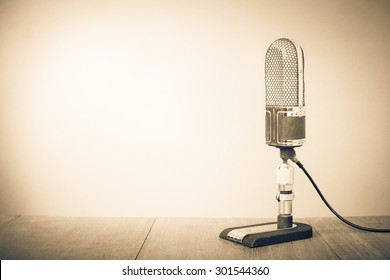 Retro old recording studio microphone from 50s on table. Vintage style sepia photo