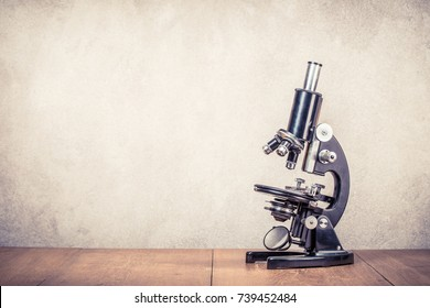 Retro old scientific laboratory microscope circa 40s on wooden table front concrete wall background. Vintage style filtered photo