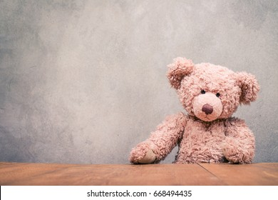 Retro old Teddy Bear toy sitting at the wooden desk front concrete wall texture background. Vintage style filtered photo