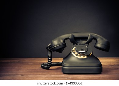 Retro old telephone on table front dark background