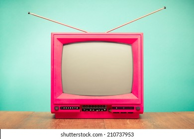 Retro old television with antenna on table front mint green background