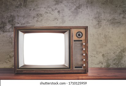 Retro old television on wooden table in front of concrete wall background, classic TV with cut out screen