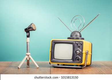 Retro old television receiver and microphone with tripod on table front gradient aquamarine wall background. Broadcasting concept. Vintage style filtered photo