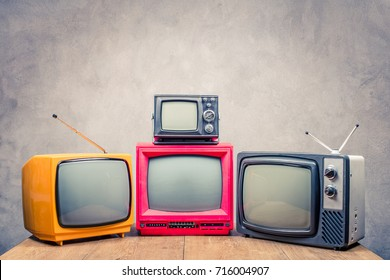 Retro old television receivers on wooden table front textured concrete wall background. TV broadcasting concept. Vintage instagram style filtered photo