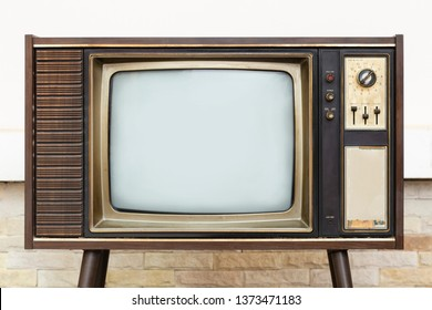 Retro, old television stands with brick wall background