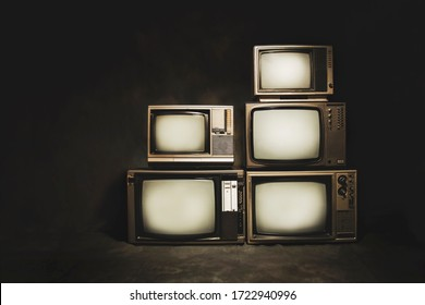 Retro old televisions pile on floor on a dark background, vintage style photo.